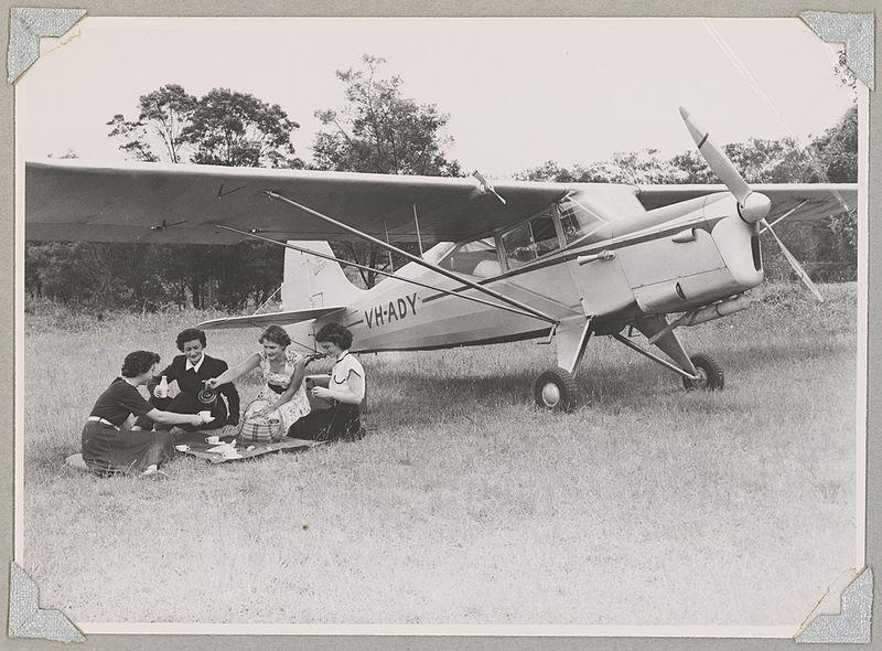 Meg Cornwell (zweite von links), Mitglied der Australian Women Pilots 'Association, und drei weitere Frauen, die auf einem Feld neben dem Auster J / 5G Cirrus Autocar-Eindecker VH-ADY, 1954, ein Picknick machen, National Library of Australia from Canberra, Australia